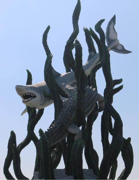 A statue of a shark and a crocodile in seaweed